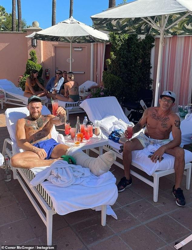 Camino a la recuperación: Conor McGregor levantó los pies relajados en la tumbona durante sus vacaciones en Los Ángeles el jueves, una semana después de una terrible rotura de pierna en UFC 264.